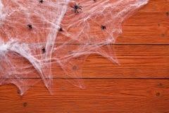 Allhelgonaaftonbakgrund med dekorativ kuslig rengöringsduk och spindlar på orange träbräden Förbigå utrymme för text Royaltyfria Bilder