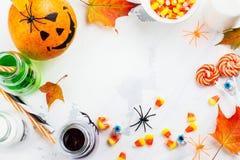 Allhelgonaaftonbakgrund med drinkar, godisar och dekoren på den vita tabellen Royaltyfri Fotografi