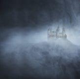 Allhelgonaaftonbakgrund med en spöklik slott på berget Arkivfoton