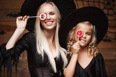 Allhelgonaaftonbegrepp - härlig caucasian moder och hennes dotter i häxadräkter som firar allhelgonaafton med allhelgonaaftongodi Arkivfoton