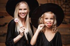 Allhelgonaaftonbegrepp - härlig caucasian moder och hennes dotter i häxadräkter som firar allhelgonaafton med allhelgonaaftongodi Fotografering för Bildbyråer