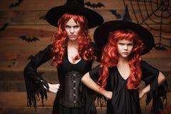 Allhelgonaaftonbegrepp - härlig caucasian moder och hennes dotter med långt rött hår i häxadräkter med ilsken petig ansikts- expr royaltyfri bild