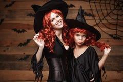 Allhelgonaaftonbegrepp - härlig caucasian moder och hennes dotter med långt rött hår i häxadräkter som firar att posera för allhe royaltyfri bild