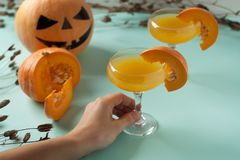 Allhelgonaaftoncoctail, orange drink för pumpa med kryddor DFestive garnering med torra blommor och pumpavakter Fotografering för Bildbyråer