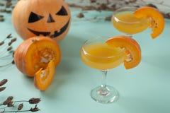 Allhelgonaaftoncoctail, orange drink för pumpa med kryddor DFestive garnering med torra blommor och pumpavakter Royaltyfri Fotografi