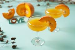 Allhelgonaaftoncoctail, orange drink för pumpa med kryddor DFestive garnering med torra blommor och pumpavakter Arkivbild