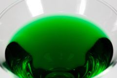 Allhelgonaaftonen inspirerade coctailen för grön färg i ett klart glass sammanträde på en vit tabell som väntar för att tyckas om royaltyfri foto