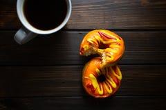 Allhelgonaaftonen och hösten färgade smakliga färgrika donuts som tjänades som för frukost på ett köksbord med att leda i rör - v royaltyfri foto