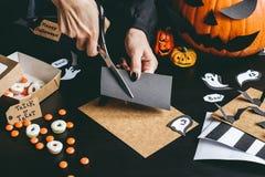 Allhelgonaaftonförberedelse Händer som gör halloween garnering genom att använda hantverket för att skyla över brister royaltyfri fotografi
