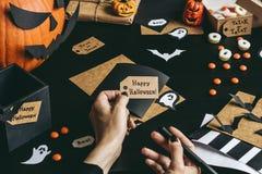 Allhelgonaaftonförberedelse Händer som gör halloween kort genom att använda hantverkpapper Arkivfoton