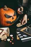 Allhelgonaaftonförberedelse Händer som gör halloween kort genom att använda hantverkpapper Fotografering för Bildbyråer