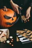 Allhelgonaaftonförberedelse Händer som gör halloween kort genom att använda hantverkpapper Royaltyfri Foto