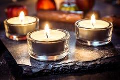 Allhelgonaaftongarnering med tre Tealights, choklad och pumpa Fotografering för Bildbyråer