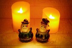 Allhelgonaaftongarneringspöke och stearinljus på väggbakgrund Royaltyfri Fotografi