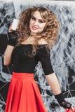 Allhelgonaaftonhäxaflicka som framme står av den svarta väggen i en blus och en röd kjol Hållande stearinljus i hand Royaltyfria Bilder