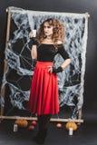 Allhelgonaaftonhäxaflicka som framme står av den svarta väggen i en blus och en röd kjol Hållande stearinljus i hand Arkivbild