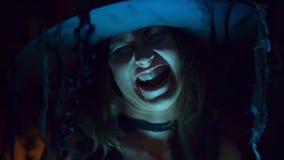 Allhelgonaaftonhäxan i en hatt skrattar scaryly och illvilligt Ruskig ondska stock video