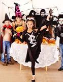 Allhelgonaaftonparti med barn som rymmer trick eller fest. Arkivbild