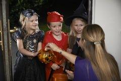 Allhelgonaaftonparti med barntrick eller behandling i dräkt Royaltyfri Foto