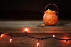 Allhelgonaaftonpumpa för litet trick som eller festfylls med godishavre på en lantlig trähylla med rad av orange ljus och mörk ba arkivbilder