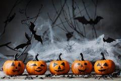 Allhelgonaaftonpumpa heads med roligt leende och spöklik garnering på mörkt trä Arkivfoton
