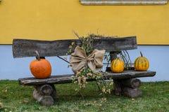 Allhelgonaaftonpumpa på en bänk med garneringar fotografering för bildbyråer