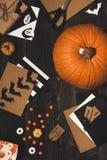 Allhelgonaaftonpumpa, sötsaker, halloween kort och garnering som göras av hantverket, skyler över brister på trätabellen Fotografering för Bildbyråer