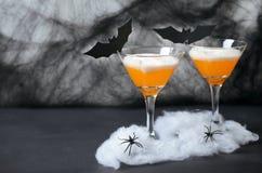Allhelgonaaftonpumpacoctail, giftlig orange drink som dekoreras med spindlar, spindelnät och svartslagträn på mörk bakgrund royaltyfria bilder
