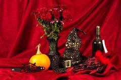 Allhelgonaaftonstilleben med pumpor, häxahatten, flaskan av vin och vasen av blommor Arkivbilder