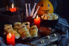 Allhelgonaaftontrick eller festparti Rolig läcker mat och pumpa på träbakgrund - mini- pizza, brödpinnar, ost, oliv, royaltyfri foto