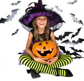 Allhelgonaaftonungar, den lyckliga läskiga flickauppklädden i den halloween dräkten av häxan, trollkarlen för pumpalapp och hallo royaltyfria bilder