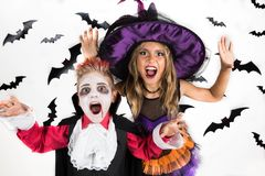Allhelgonaaftonungar, lycklig läskig flicka och pojkeuppklädd i halloween dräkter av häxan, trollkarlen och vampyren Dracula för  royaltyfria bilder