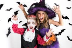 Allhelgonaaftonungar, lycklig läskig flicka och pojkeuppklädd i halloween dräkter av häxan, trollkarlen och vampyren Dracula för  royaltyfri bild