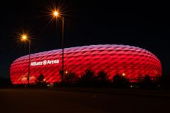 Allianz Arena, the football stadium of FC Bayern, illuminated in red at night. MUNICH, GERMANY - 29 April 2018: Allianz Arena, the football stadium of FC Bayern royalty free stock photo