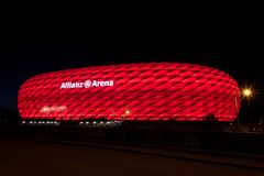 Allianz Arena, the football stadium of FC Bayern, illuminated in red at night. MUNICH, GERMANY - 29 April 2018: Allianz Arena, the football stadium of FC Bayern stock photo