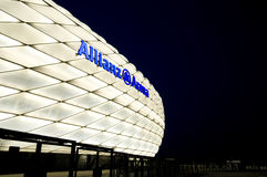 Allianz Arena lit in white. Famous landmark, exterior of the Allianz Arena in Munich, Germany. Night shot, the arena lit with white light, night sky as space for stock photo