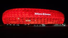 Allianz arena som är upplyst på natten arkivfoton