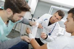 Allieva infermiera che benda il polso paziente del ` s nell'ambito del controllo fotografia stock