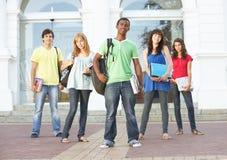 Allievi adolescenti che si levano in piedi la costruzione esterna dell'istituto universitario Immagine Stock Libera da Diritti