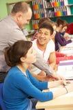 Allievi adolescenti che studiano nell'aula con l'insegnante privato Immagine Stock