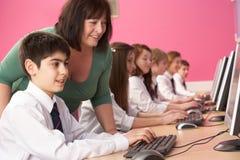 Allievi adolescenti in ESSO codice categoria che per mezzo dei calcolatori Fotografie Stock Libere da Diritti