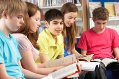 Allievi adolescenti in libri di lettura delle biblioteche Fotografie Stock Libere da Diritti