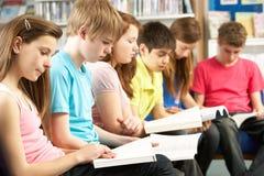 Allievi adolescenti in libri di lettura delle biblioteche Immagini Stock Libere da Diritti
