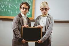 Allievi agghindati come insegnanti che tengono lavagna Fotografia Stock Libera da Diritti