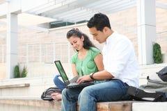 Allievi al banco che studiano sul computer portatile Immagine Stock Libera da Diritti