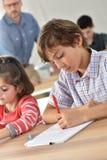 Allievi alla scuola che imparano e che scrivono Fotografia Stock