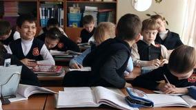 Allievi alla scuola che si siede nella classe video d archivio