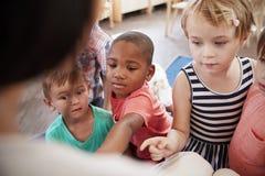 Allievi alla scuola di Montessori che esamina libro con l'insegnante Immagini Stock