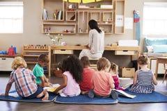 Allievi alla scuola di Montessori che leggono indipendente nell'aula Immagine Stock