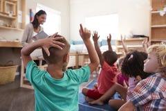 Allievi alla scuola di Montessori che solleva le mani per rispondere alla domanda Fotografia Stock Libera da Diritti